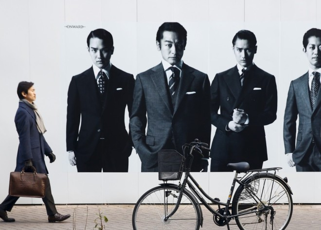 A man walks past an advertisement of a luxury men's fashion boutique in the Ginza shopping district in Tokyo